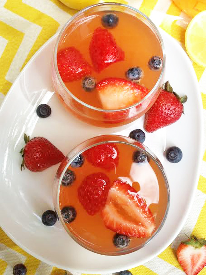 Overhead shot of two glasses filled with Strawberry Infused lemonade garnished with sliced strawberries and blueberries on a white platter.
