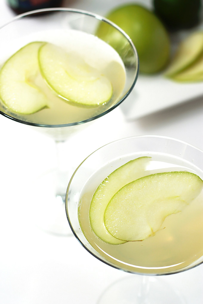 Apple Beer Cocktails in two martini glasses garnished with apple slices.