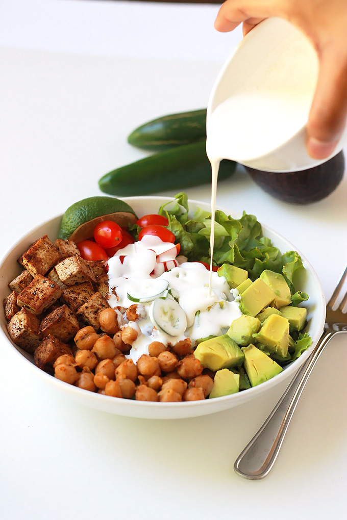 Pouring sauce over Spicy chickpea burrito bowl salad.