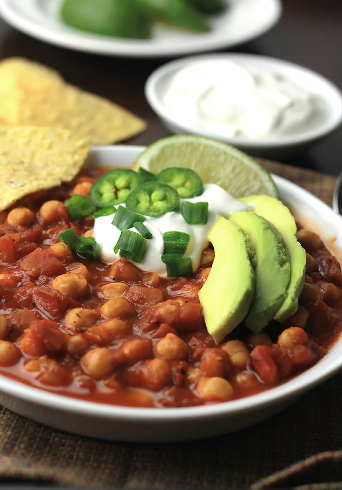 Bowl of Chickpea Chili topped with vegan sour cream, sliced avocado, jalapeno, scallions and a wedge of lime.