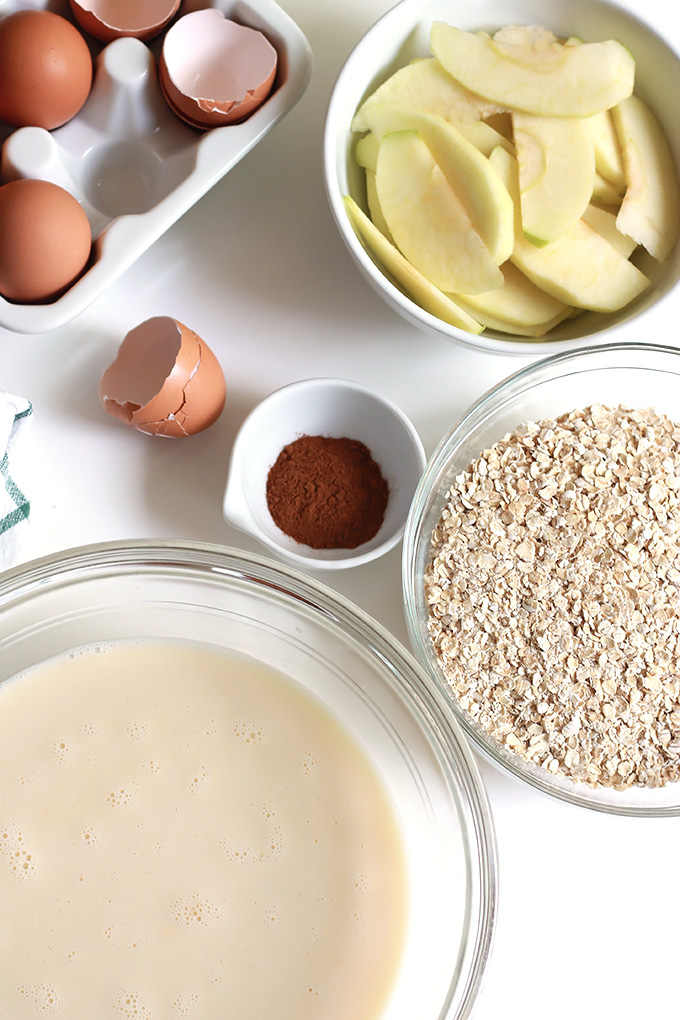 Above cracked eggs shells, bowl of sliced apples, bowl of oats and bowl of almond milk.