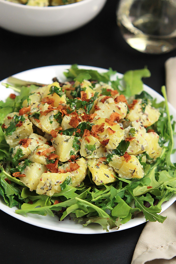 Vegan Yukon Kale Potato Salad on a bed of arugula with coconut bacon on top.