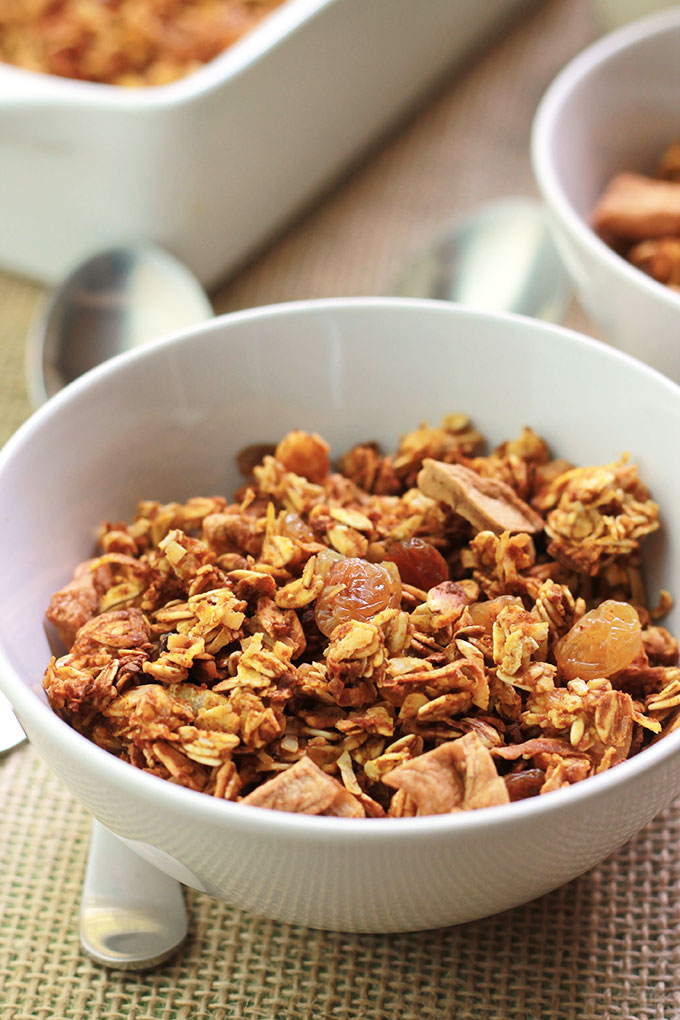 Pumpkin Apple Cinnamon Granola in a white bowl with spoon beside bowl.