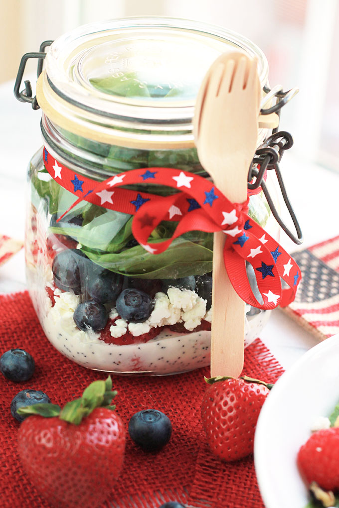 Layers of fruit, creamy goat cheese and lettuce, this Red White & Blue Salad with Poppy Seed Dressing is colorful and perfect for patriotic celebrations.