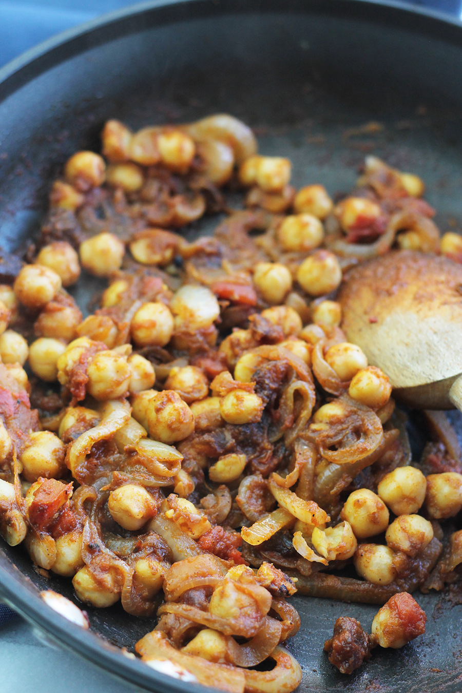 Chickpeas in saute pan, seasoned with Moroccan inspired spice blend.