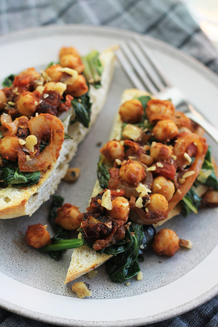 close-up shot of ciabatta garlic toast with spinach, chard and chickpeas on top.