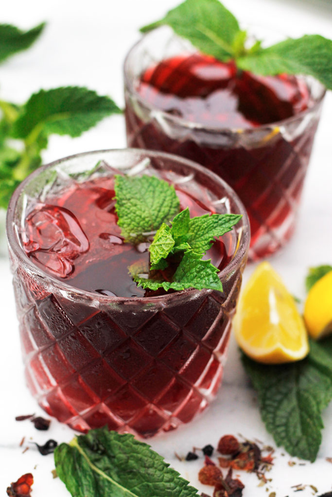 Two glasses of Sweet Vermouth Hibiscus Tea Cocktail garnished with fresh mint, with mint sprigs and sliced lemons beside the glass.