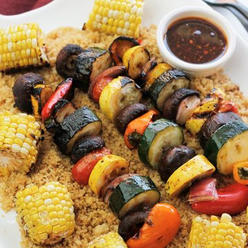 Overhead shot of grilled veggie kabobs, corn over couscous.
