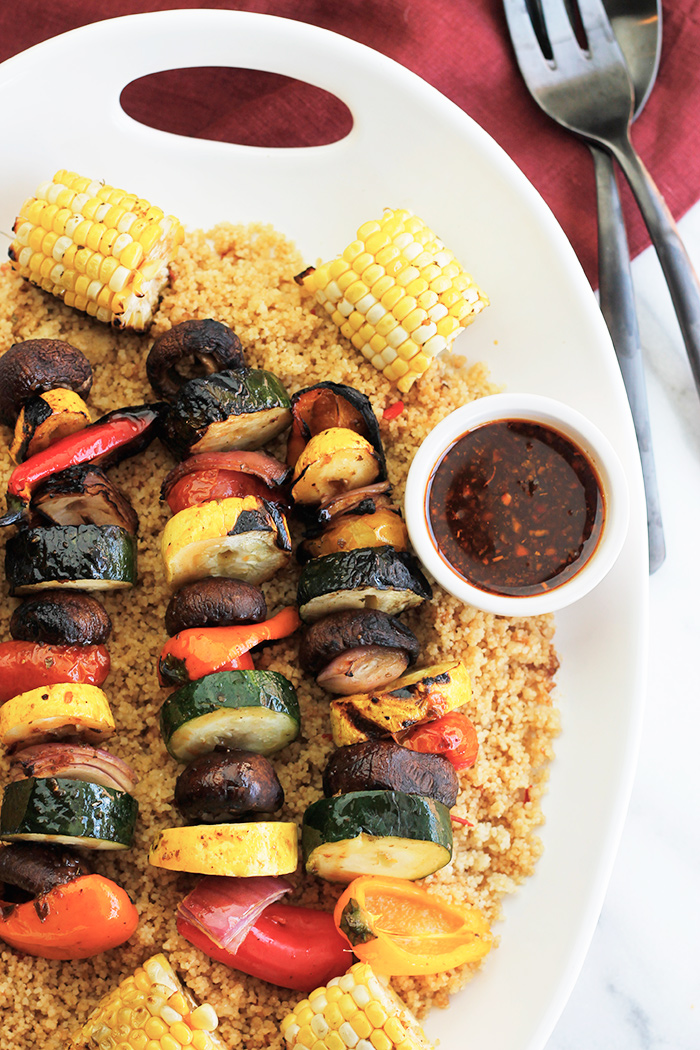 Overhead shot of Harissa Spiced Grilled Veggie Kabobs and corn over bed of couscous.