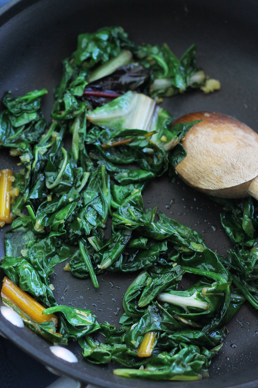 Spinach and chard in saute pan with wooden spoon on the side.