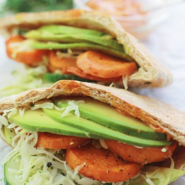 Spicy roasted sweet potatoes, cucumber slaw, and avocado slices inside pita pocket.