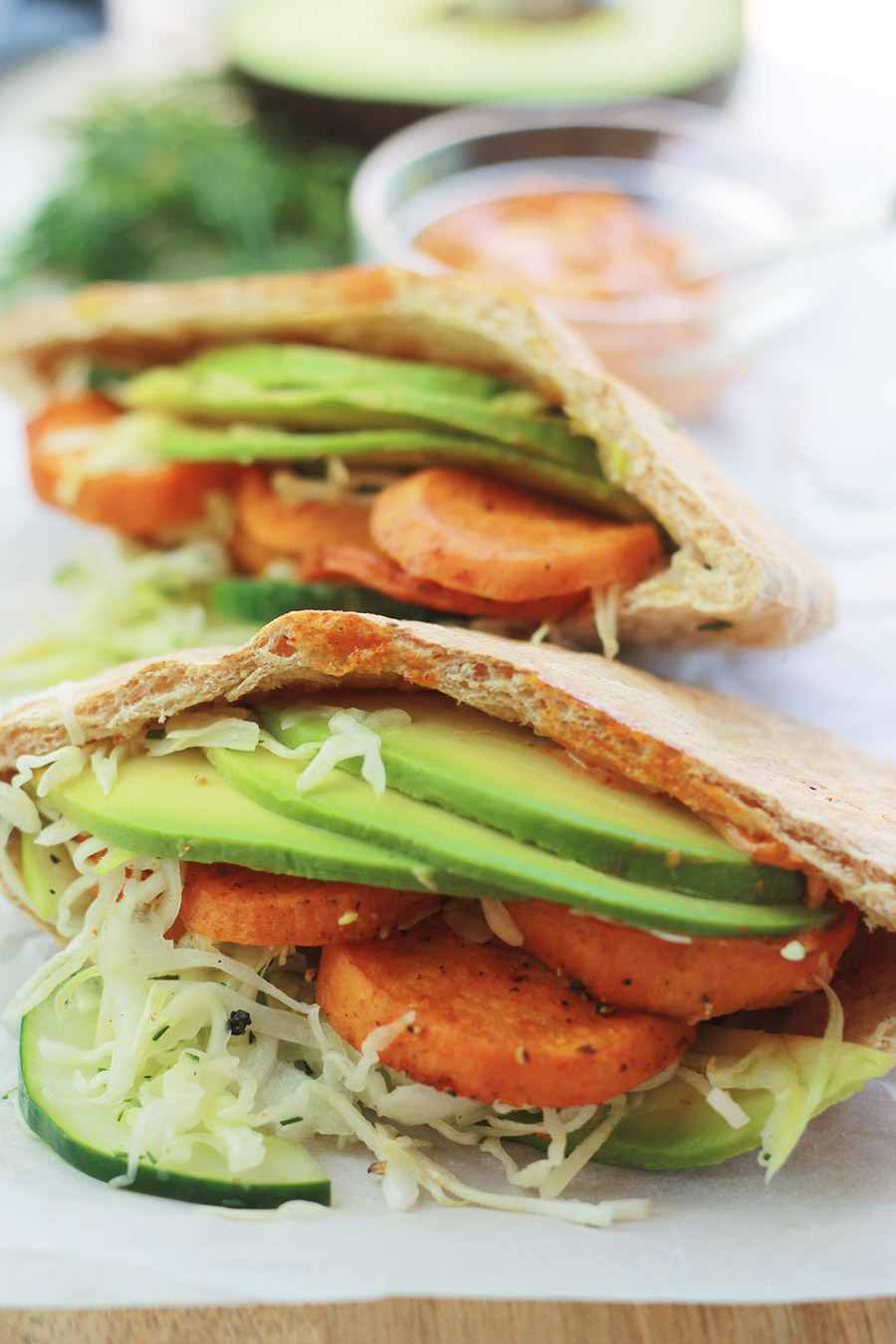 Pita pocket stuffed with spicy roasted sweet potato slices, cucumber slaw and avocado slices, with half of an avocado slice and sandwich spread in background.