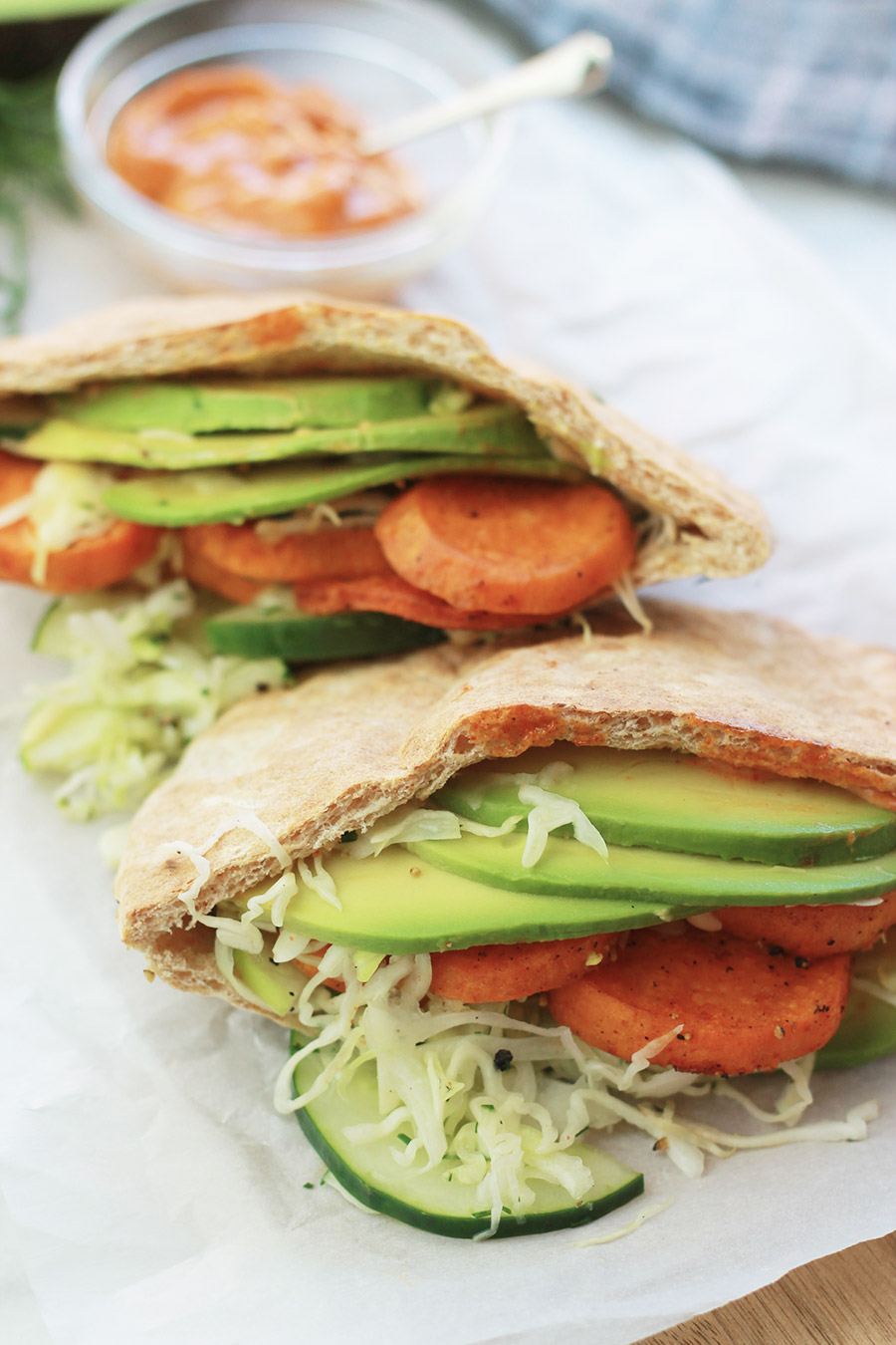 Close-up of pita pocket stuffed with spicy roasted sweet potato slices, cucumber slaw and avocado slices, with sandwich spread in background.