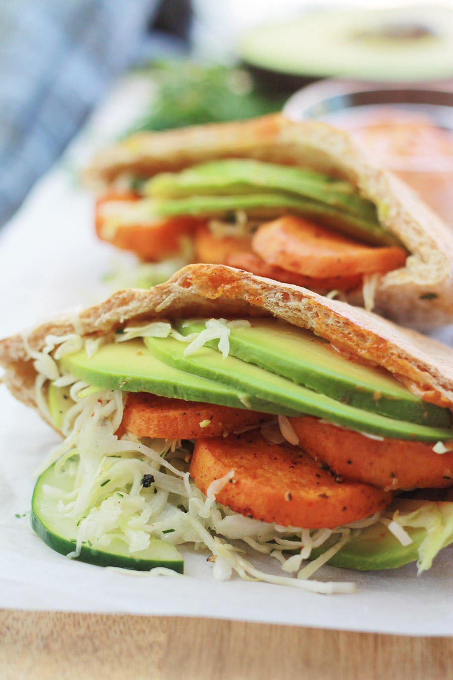 Close-up of pita pocket stuffed with spicy roasted sweet potato slices, cucumber slaw and avocado slices, with half of an avocado slice and sandwich spread in background.