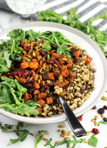 Bowl of grains with roasted butternut squash and arugula.