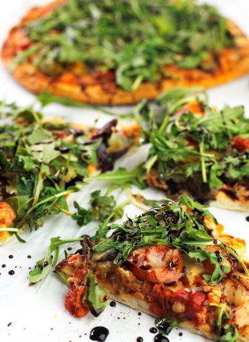 Slices of roasted veggie pizzas topped with arugula greens and drizzled with balsamic glaze.