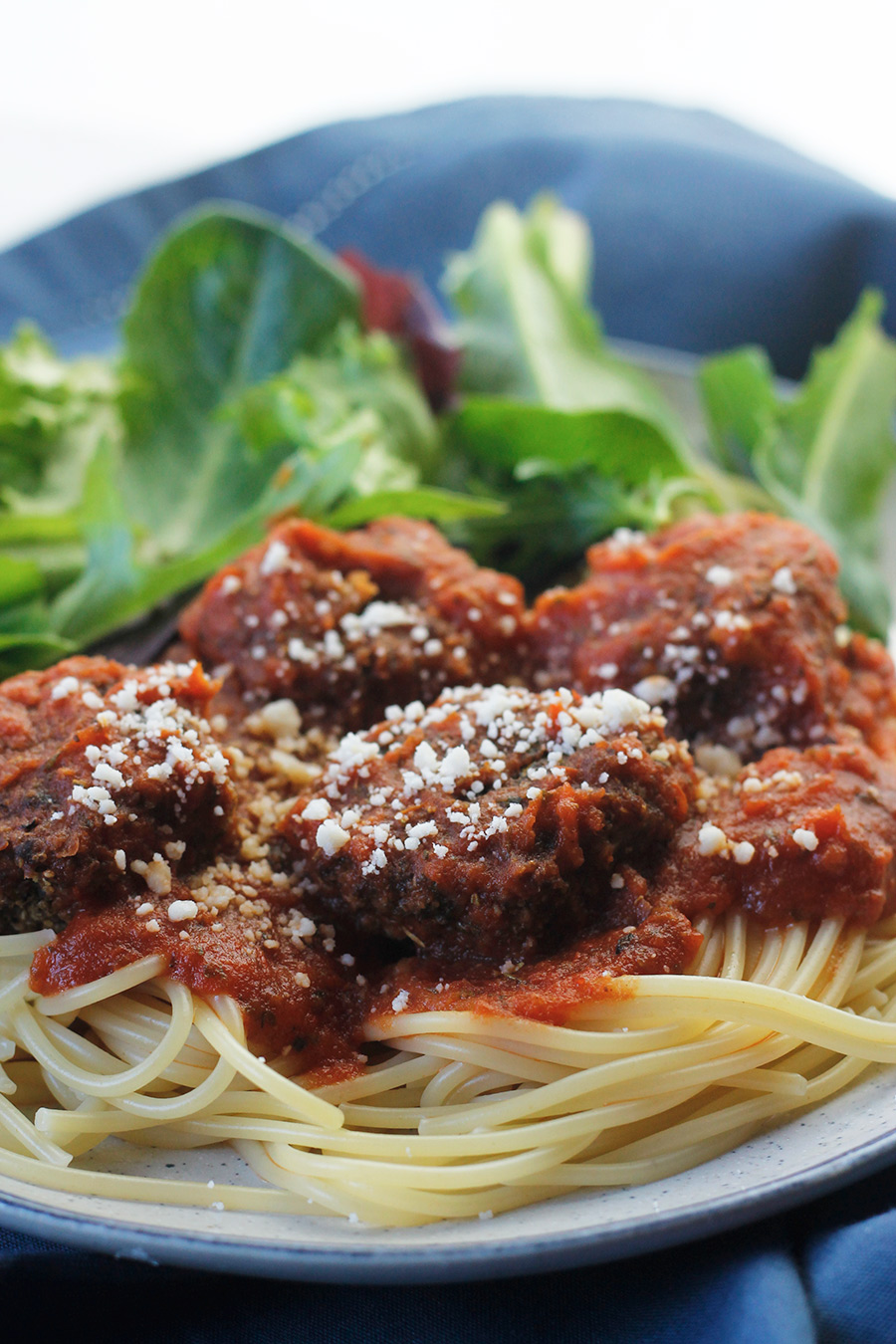 Close-up of easy meatless meatballs over pasta and pasta sauce.