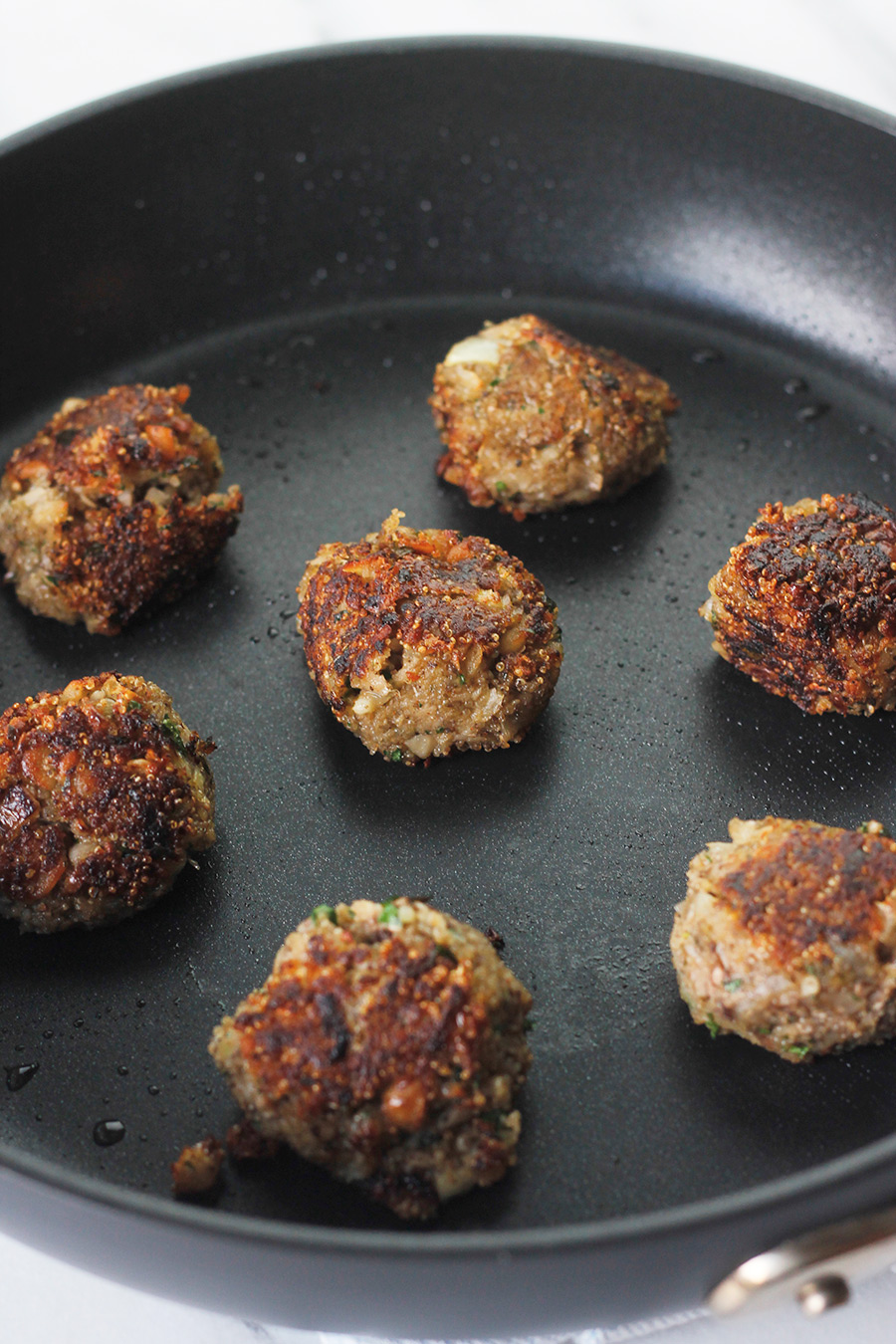 Easy meatless meatballs cooking in nonstick skillet.