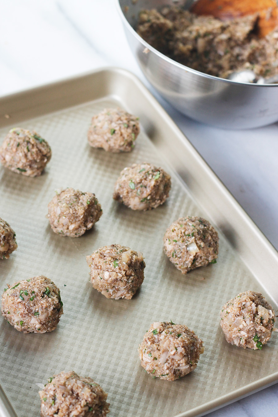 Uncooked meatless meatballs on shallow baking pan.