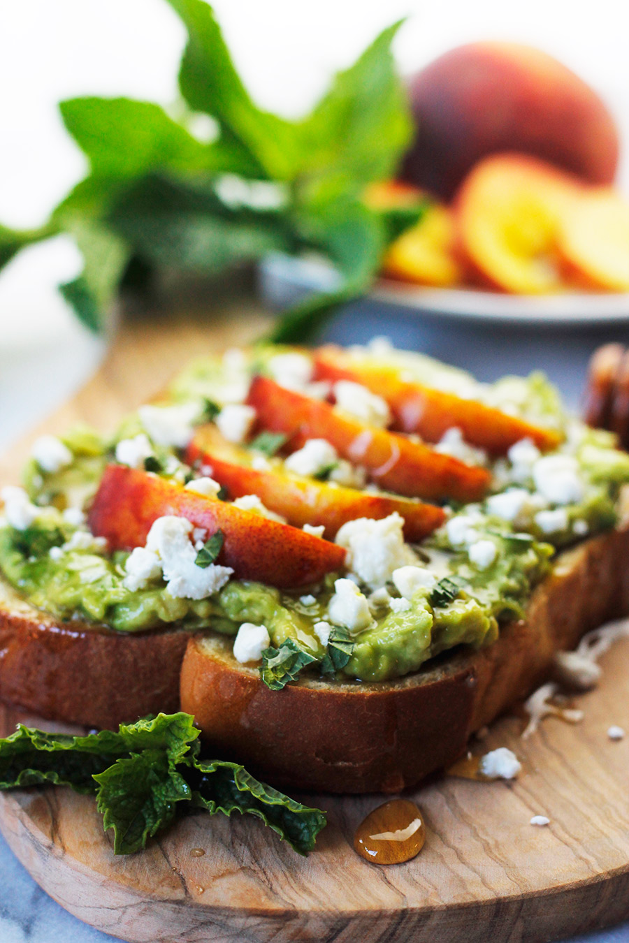 Avocado toast topped with sliced peaches, sprinkled with goat cheese, fresh torn mint leaves and drizzled with honey