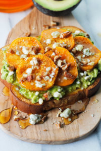 Avocado toast topped with roasted sweet potato rounds sprinkled blue cheese, pecans and drizzled with honey,